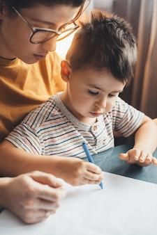 Primo piano foto di una madre caucasica con gli occhiali, aiutando il figlio a fare i compiti