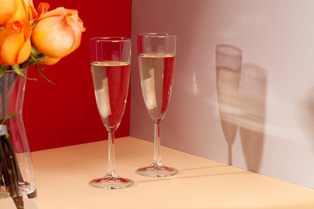 Chiuda sulla foto dei vetri del champagne con le rose in un vaso
