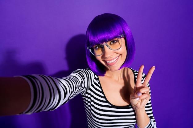 Close up foto di affascinante ragazza che fa foto v-segno sorridente isolato su sfondo viola viola