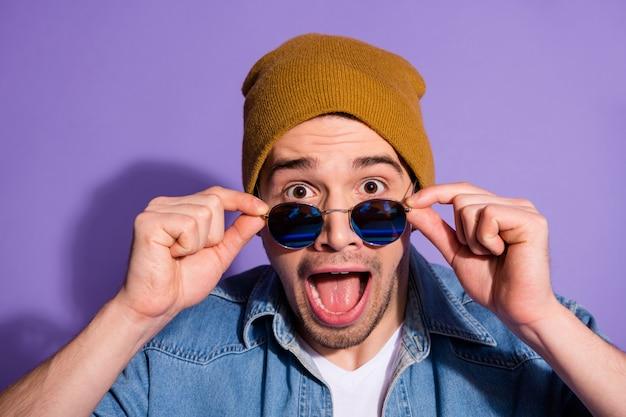 Close up foto di allegro eccitato divertente esultante ragazzo che indossa il cappuccio copricapo occhiali occhiali da vista gridando omg in denim isolato su sfondo di colore viola vivido