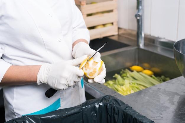 Chiuda sulla foto dello chef che pulisce il limone in cucina