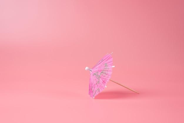 Foto ravvicinata dell'ombrello rosa cocktail isolato su sfondo rosa