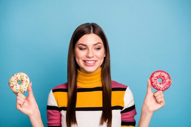 Close up foto di contenuto ragazza tenere due ciambelle guardare vuole mangiare gustoso fast food indossare moderno vestito colorato isolato su parete di colore blu