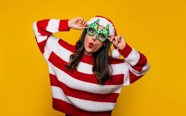 Foto ravvicinata di una donna moderna e pazza con divertenti occhiali di natale e cappello di babbo natale si sta divertendo mentre posa contro un muro giallo
