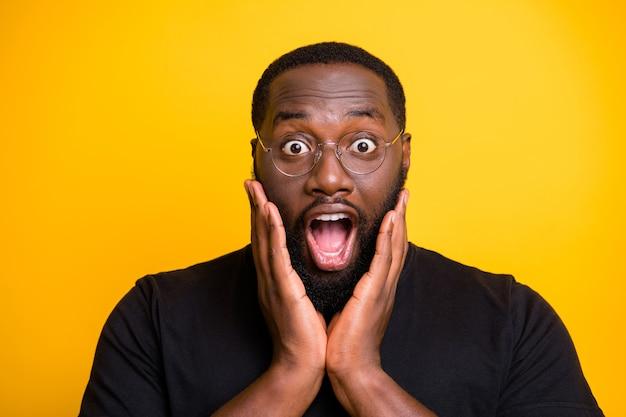 Chiuda sulla foto dell'uomo nero di stupore urlante pazzo in maglietta che esprime stupore sulla parete gialla di colore brillante isolata del fronte