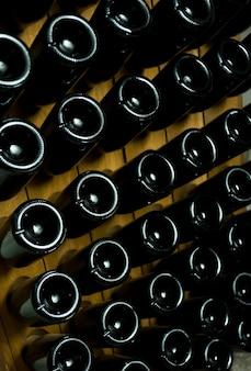 Close up foto di bottiglie scure di vino posa sotterranea, cantina autunno concetto