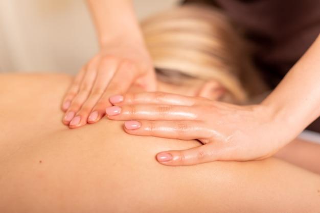 Primo piano foto del massaggio dei tessuti profondi. massaggiatrice che fa massaggio alle spalle e alla schiena. cliente sdraiato e rilassante