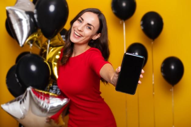 Foto ravvicinata di una bella giovane donna eccitata in un vestito rosso alla moda mentre mostra il telefono sulla fotocamera con i tanti palloncini nel venerdì nero su sfondo giallo