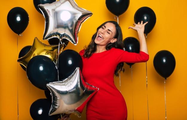 Foto ravvicinata di una giovane donna alla moda carina eccitata in un vestito rosso alla moda mentre si diverte e posa con i tanti palloncini nel venerdì nero su sfondo giallo