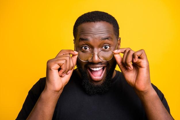 Chiuda sulla foto dell'uomo di colore divertente eccitato che indossa occhiali da vista per la prima volta vedendo i suoi amici parete di colore brillante isolata in modo dettato