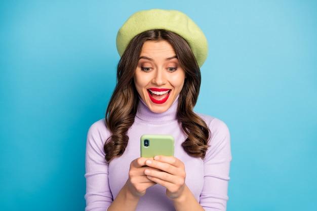 Chiuda sulla foto eccitata ragazza dipendente dalla rete sociale utente leggere smartphone incredibile notifica urlo wow omg indossare vestiti alla moda viola verde alla moda isolato muro di colore blu