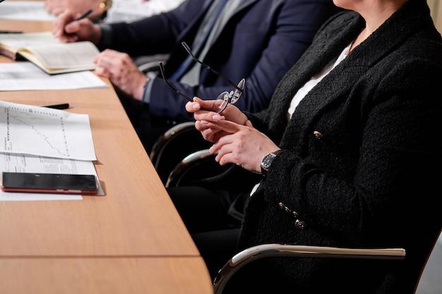 Foto del primo piano delle mani femminili che tengono gli occhiali nelle mani alla riunione, in ufficio, seduto alla scrivania