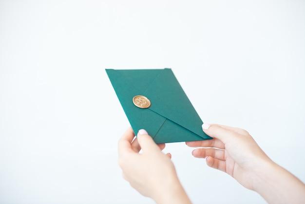 Foto del primo piano delle mani femminili che tengono una busta verde dell'invito con un sigillo di cera, un buono regalo, una cartolina, una carta dell'invito di nozze.