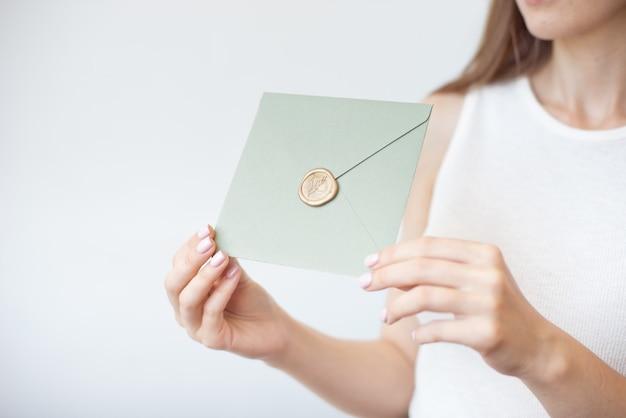 Foto del primo piano delle mani femminili che tengono una busta blu o rosa d'argento dell'invito con un sigillo di cera, un buono regalo, una cartolina, una carta dell'invito di nozze.