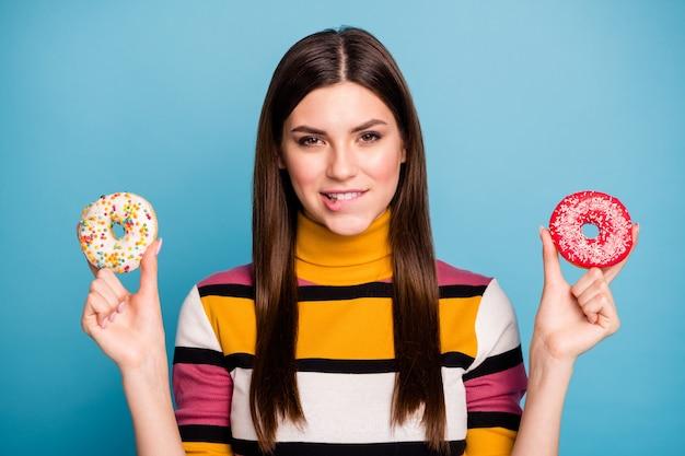 Close up foto di flirty ragazza attraente tenere due ciambelle voglio mangiare sentire sogno desiderio morso denti labbra indossare un bell'aspetto ponticello isolato su parete di colore blu