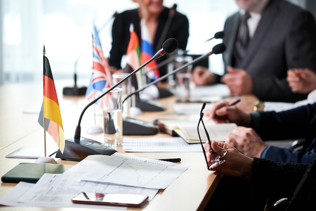 Foto ravvicinata, messa a fuoco sui microfoni, uomini d'affari seduti davanti ai microfoni mentre partecipano alla conferenza stampa
