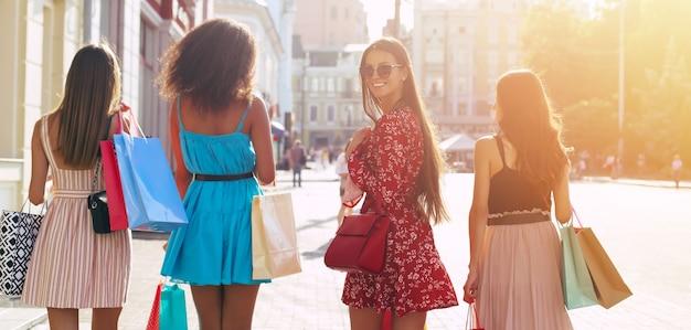 Foto ravvicinata di quattro ragazze che camminano lungo le strade della città portando borse della spesa con le spalle alla telecamera
