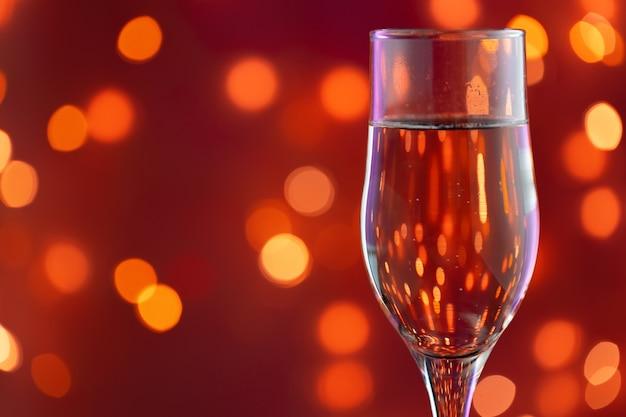 Primo piano foto del bicchiere pieno di champagne contro luci sfocate