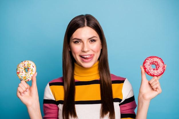 Close up foto di funky emozioni positive ragazza tenere due pasticcini biscotti zuccherini leccare le labbra vogliono mangiare indossare uno stile casual ponticello isolate su colore blu parete