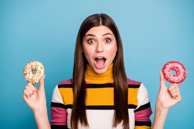 Close up foto di divertente stupito lady si sente affamato prendi due ciambelle urlare wow omg indossare ponticello stile casual isolato su parete di colore blu