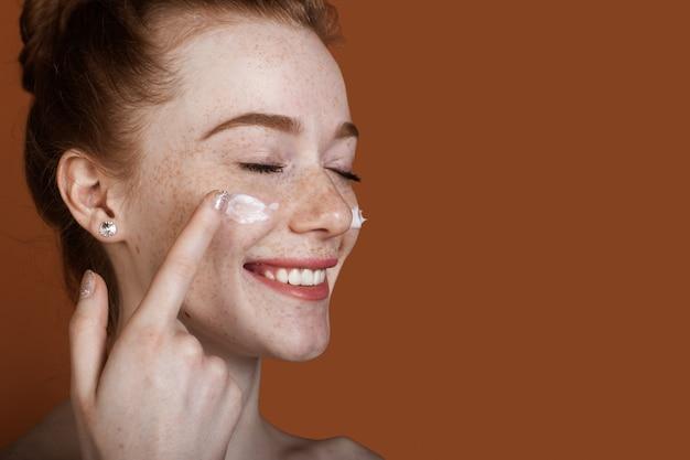 Chiuda sulla foto di una donna allo zenzero con le lentiggini e le spalle nude che applica una crema sul viso su una parete marrone con spazio libero