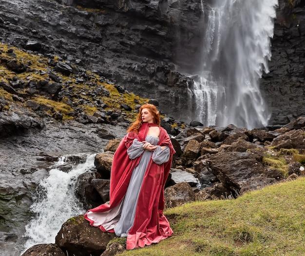 Close up foto ragazza in un mantello rosso rimane vicino alla cascata di fossa, streymoy, isole faerøer
