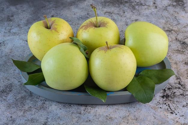 Chiuda sulla foto delle mele fresche verdi sul vassoio di legno grigio.