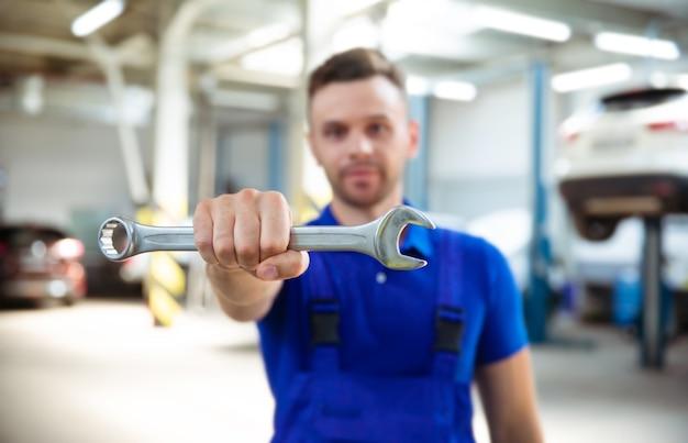 Foto ravvicinata di un meccanico felice con una chiave inglese in mano sullo sfondo della riparazione di un'auto
