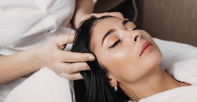 Da vicino la foto di una sessione di massaggio alla testa fatta presso il centro termale di una donna bruna sdraiata con gli occhi chiusi