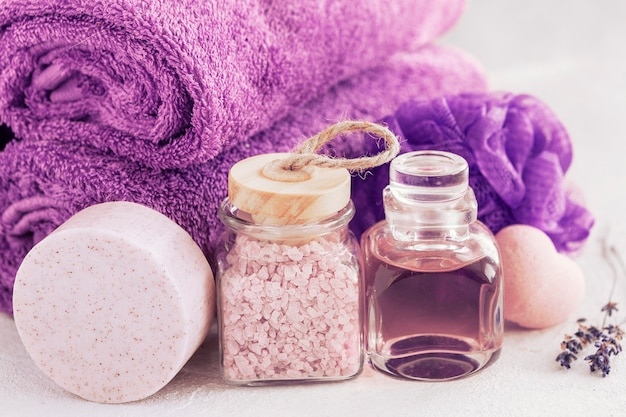 Primo piano foto di sale da bagno aromatico alla lavanda, essenza, sapone, spugna per il corpo e asciugamani. concetto di benessere per spa, salone di bellezza e salute, negozio di cosmetici.