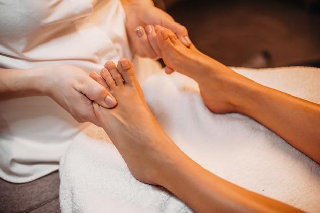 Primo piano foto di un massaggio alle gambe presso la spa eseguito da un massaggiatore esperto