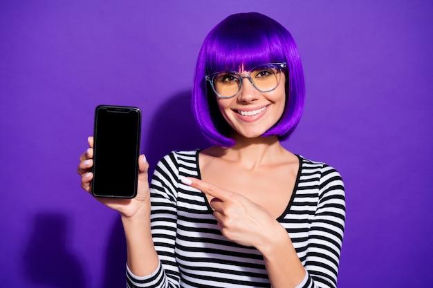 Close up foto della bella gioventù dispositivo di contenimento pubblicità indossando occhiali occhiali camicia a righe isolate su sfondo viola viola