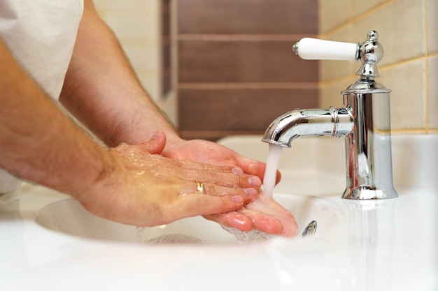 Chiuda sulla foto delle mani maschii che lavano con sapone sopra il lavandino all'interno
