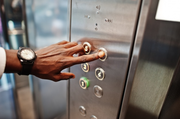 Chiuda sulla foto della mano dell'uomo con gli orologi all'elavatore o all'ascensore moderno, spingendo il bottone