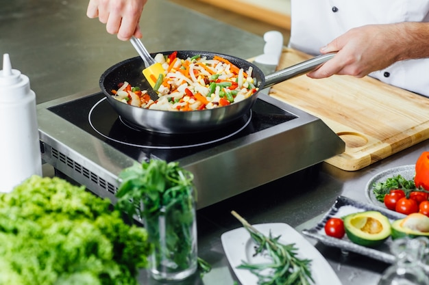 Close up foto, mani dell'uomo con grembiule frittura di verdure, cucina moderna