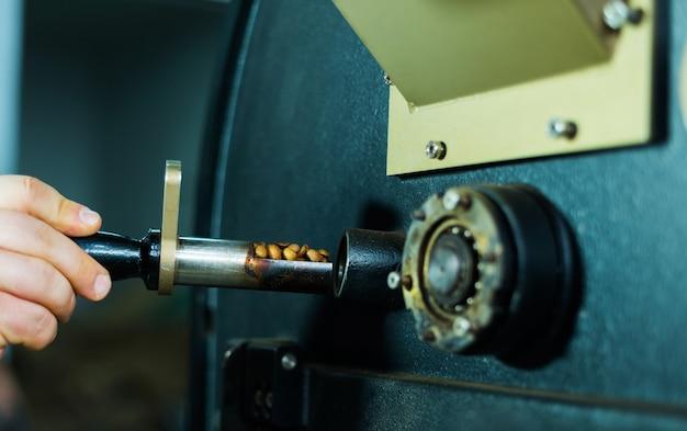Close up foto di un uomo che guarda i chicchi di caffè tostati. preparare i fagioli per una bevanda straordinaria.