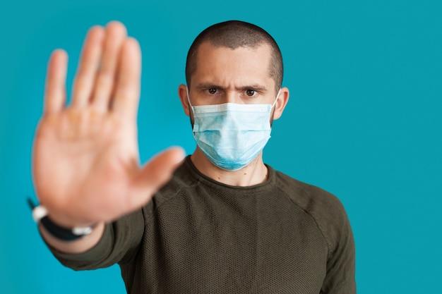 Chiudere la foto di un uomo in maglione che indossa una maschera medica su un muro blu studio gesticolando stop e segno di rifiuto con il palmo