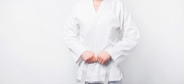 Close up foto di uomo che indossa taekwondo dobok uniforme sul muro bianco