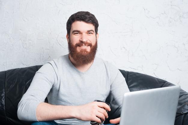 Chiuda sulla foto dell'uomo con la barba che si siede sul sofà e che tiene la tazza di caffè