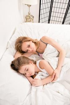 Chiuda sulla foto della figlia della madre e del bambino che dorme nel letto
