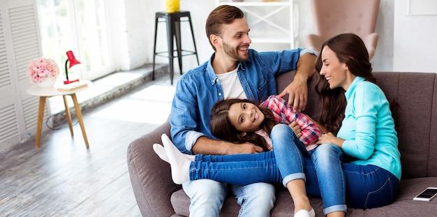 Foto ravvicinata di madre, padre e figlia che posano insieme per una foto comune nel loro elegante soggiorno, abbracciati con sorrisi radiosi