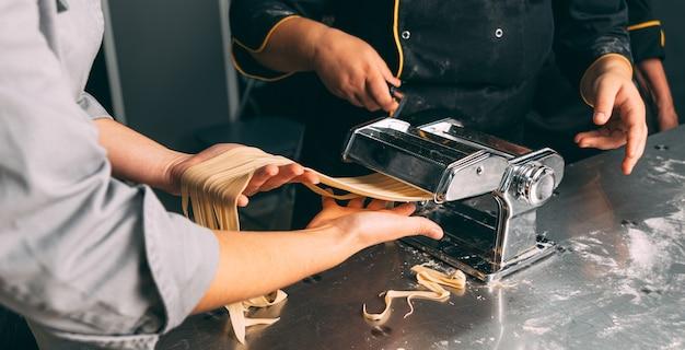 Foto ravvicinata del processo di produzione della pasta in una cucina professionale.