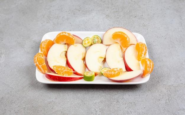 Primo piano foto del mucchio di fette di frutta fresca sulla piastra bianca.