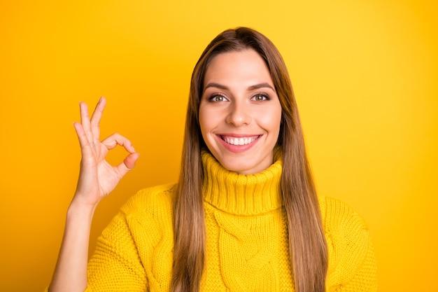 Close up foto di positivo ragazza allegra promotore mostra segno ok consiglia scegliere pubblicità promozione indossare pullover stile casual isolato su lucentezza parete a colori