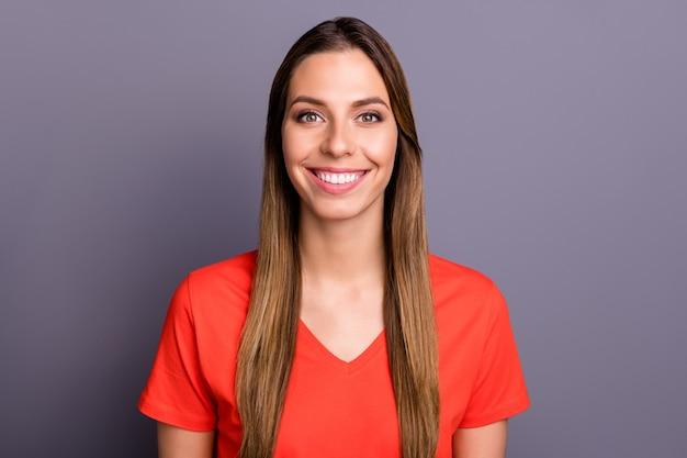Close up foto di bella mora signora in maglietta rossa in posa contro il muro viola