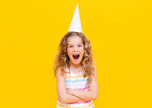 Foto ravvicinata di una bambina piuttosto scioccata con la bocca aperta, festa, berretto di compleanno di carta, sfondo giallo brillante isolato