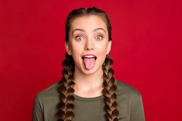 Chiuda sulla foto della signora modello abbastanza teenager che gioca con il compagno di classe che attacca la lingua fuori la bocca indossa il pullover casual isolato di colore rosso di sfondo