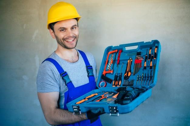 La foto ravvicinata di un riparatore professionista in uniforme e casco di sicurezza tiene in mano nuovi strumenti moderni per il lavoro e la ristrutturazione