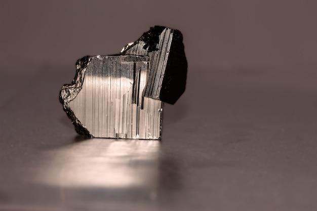 Foto ravvicinata di un minerale di pirite sulla superficie riflettente. si presenta in cristalli cubici, pentagonododecaedrici o ottaedrici, a volte con facce alternate striate longitudinalmente