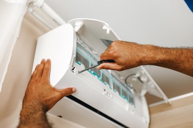 Close up foto del riparatore che fissa il condizionatore d'aria in una stanza